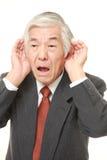 Homme d'affaires japonais supérieur avec la main derrière l'oreille écoutant étroitement Photo stock