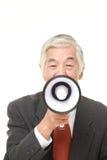 Homme d'affaires japonais supérieur avec le mégaphone Photographie stock