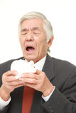 Homme d'affaires japonais supérieur avec une allergie éternuant dans le tissu Photos libres de droits