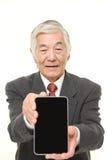 Homme d'affaires japonais supérieur tenant une tablette Image libre de droits