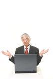 Homme d'affaires japonais supérieur utilisant l'ordinateur semblant confus Image stock