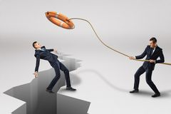 Homme d'affaires jetant la bouée de sauvetage orange à un autre homme d'affaires qui tombe dans la fente de tremblement de terre  photo libre de droits