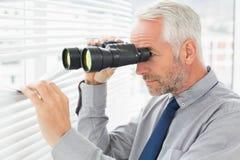 Homme d'affaires jetant un coup d'oeil avec des jumelles par des abat-jour Photos libres de droits