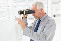 Homme d'affaires jetant un coup d'oeil avec des jumelles par des abat-jour dans le bureau Photographie stock libre de droits