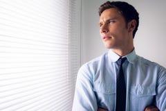 Homme d'affaires jetant un coup d'oeil par des abat-jour dans le bureau Image stock