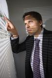 Homme d'affaires jetant un coup d'oeil par des abat-jour dans le bureau Image libre de droits