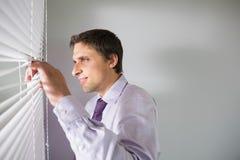 Homme d'affaires jetant un coup d'oeil par des abat-jour dans le bureau Images libres de droits