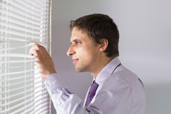 Homme d'affaires jetant un coup d'oeil par des abat-jour dans le bureau Photo stock