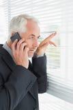 Homme d'affaires jetant un coup d'oeil par des abat-jour tandis qu'à l'appel dans le bureau Image libre de droits