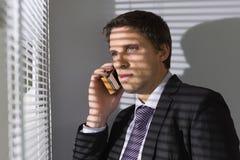 Homme d'affaires jetant un coup d'oeil par des abat-jour tandis qu'à l'appel dans le bureau Photos stock