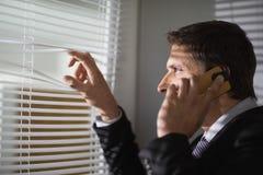 Homme d'affaires jetant un coup d'oeil par des abat-jour tandis qu'à l'appel dans le bureau Photographie stock