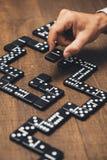 Homme d'affaires jouant avec des dominos Image stock