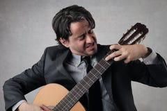 Homme d'affaires jouant la guitare Photo stock