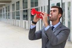 Homme d'affaires jouant la trompette d'isolement Photographie stock libre de droits