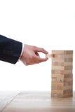 Homme d'affaires jouant le jeu en bois de blocs d'isolement sur le blanc Photo libre de droits