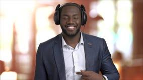 Homme d'affaires joyeux écoutant la musique dans des écouteurs banque de vidéos