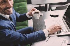 Homme d'affaires joyeux appréciant la boisson chaude pendant le travail en ligne Photos libres de droits