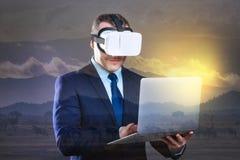 Homme d'affaires joyeux travaillant sur l'ordinateur portable tout en utilisant le casque de VR photographie stock libre de droits