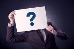 Homme d'affaires jugeant de papier avec des points d'interrogation Photographie stock