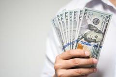 Homme d'affaires jugeant l'argent de dollar US disponible sur le fond blanc Image stock