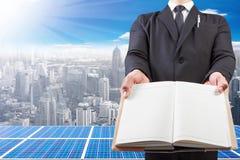 Homme d'affaires jugeant le livre panneaux vides et à énergie solaire sur la haute Photos libres de droits