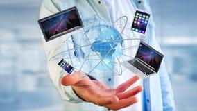 Homme d'affaires jugeant un ordinateur et des dispositifs montrés sur un futuri Photographie stock