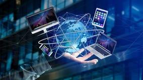 Homme d'affaires jugeant un ordinateur et des dispositifs montrés sur un futuri Photographie stock libre de droits