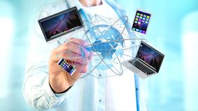 Homme d'affaires jugeant un ordinateur et des dispositifs montrés sur un futuri Photo stock