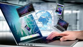 Homme d'affaires jugeant un ordinateur et des dispositifs montrés sur un futuri Image stock