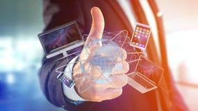 Homme d'affaires jugeant un ordinateur et des dispositifs montrés sur un futuri image libre de droits