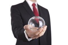 Homme d'affaires jugeant une boule en verre d'isolement sur le blanc Photographie stock