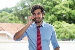 Homme d'affaires latin riant avec la barbe au téléphone portable images libres de droits