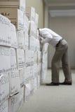 Homme d'affaires Leaning Over Boxes dans la salle d'entreposage photo libre de droits