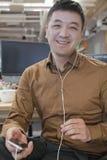 Homme d'affaires Listening Music dans le bureau Photo stock