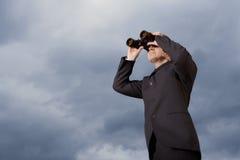 Homme d'affaires Looking Through Binoculars contre le ciel Images stock