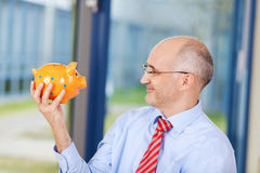 Homme d'affaires Looking At Piggybank dans le bureau Image stock