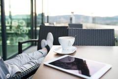 Homme d'affaires méconnaissable avec un comprimé en café de dessus de toit Photo stock