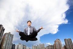 Homme d'affaires méditant dans le ciel Photos stock