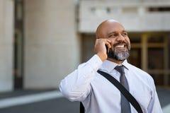 Homme d'affaires mûr africain parlant au téléphone extérieur photographie stock