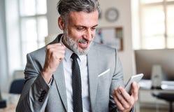Homme d'affaires mûr avec le smartphone se tenant dans un bureau, exprimant l'excitation images stock