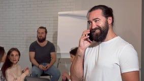 Homme d'affaires mûr barbu parlant dans le téléphone joyeux banque de vidéos