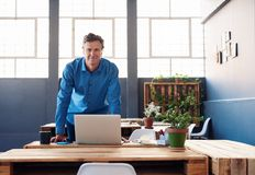 Homme d'affaires mûr de sourire se tenant à son bureau dans un bureau Photo stock