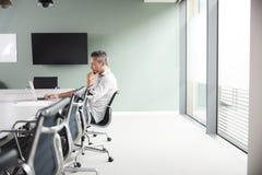 Homme d'affaires mûr en passant habillé Working On Laptop au Tableau de salle de réunion dans le lieu de réunion image libre de droits