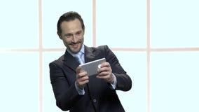 Homme d'affaires mûr enthousiaste jouant le jeu mobile banque de vidéos
