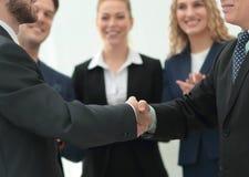 Homme d'affaires mûr serrant la main de son associé avec des collègues Photographie stock libre de droits