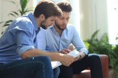 Homme d'affaires mûr utilisant un comprimé numérique pour discuter l'information avec un plus jeune collègue dans un local commer photo stock
