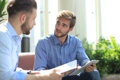 Homme d'affaires mûr utilisant un comprimé numérique pour discuter l'information avec un plus jeune collègue dans un local commer images stock