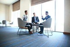 Homme d'affaires mûr utilisant un comprimé numérique pour discuter l'information avec un plus jeune collègue dans un salon modern photographie stock