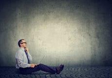 Homme d'affaires mûres avec l'ordinateur portable se reposant sur une pensée de plancher photos stock