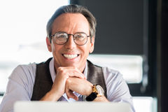 Homme d'affaires mûr agréable s'asseyant à la table avec le sourire Image stock